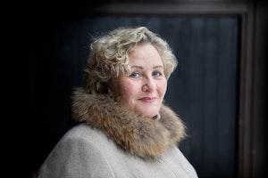 Lisbeth står foran en tredør, ikledd en kåpe med pelskrage, og smiler lett mot kameraet.
