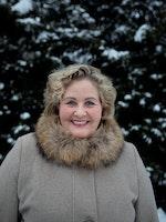 Lisbeth Wathne Svinø smilende i beige vinterkåpe med pelskrage foran en mørkegrønn hekk med snø på