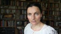 Portrett av Maja Ratkje foran bokhyller