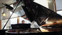 Pianist titter opp bak et stort, åpent flygel