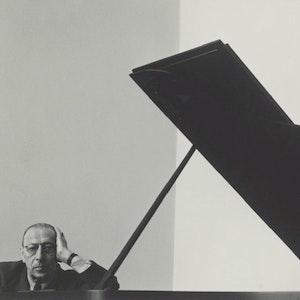 Stravinskij som lener seg på et flygel