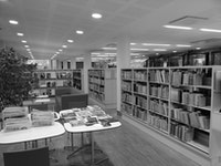 Bibliotekets sitteområde med bord, stoler, hyller og en mengde av lesestoff.