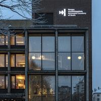 Den høyeste delen av NMHs fasade i mørket. Rett under taket står lyser logoen opp.