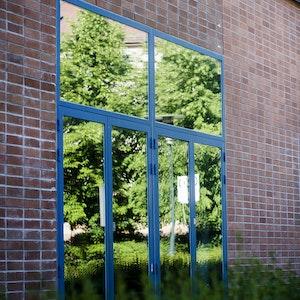 En av glassdørene ute på NMHs fasade. Det vårlige gresset speiler seg i døren.