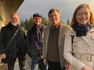 Tre menn og en dame står ute ikledd jakker og smiler mot kameraet.