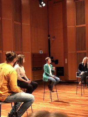 4 personer diskuterer sittende på stoler