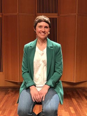 Kvinne med grønn jakke smiler og ser inn i kamera