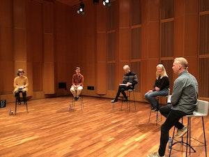 fem mennesker diskutere sittende på stoler