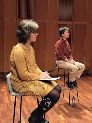 Dame i gul kjole og dame lenger bak sittende på stoler.