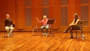 Tre mennesker sittende på stoler snakker sammen