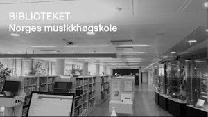 """Reoler fulle av bøker og noter, samt utstillingsmontre med historiske instrumenter. Over bildet står det """"Biblioteket, Norges musikkhøgskole""""."""