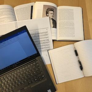 To pensumbøker og to notatblokker ligger oppslått på en bord. Ved siden av står en laptop med Word-programmet åpnet.