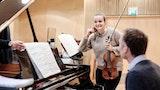 En student står ved siden av et flygel og smiler. Hun har en fiolin i hånda og ved pianoet sitter en akkopagnatør.