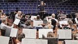 Et stort orkester spiller foran en dirigent. Bak dirigenten er det tomme seter.