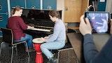 En student sitter og spiller piano, en spiller på en tromme og en tredje filmer med et nettbrett.