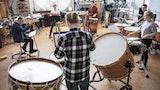Fem studenter står i ring og spiller på ulike trommer i et øvingsrom. Læreren sitter i midten og leser fra et notark.