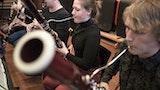 Fem studenter sitter på rad og rekke og spiller konsentrert på diverse treblåsinstrumenter.