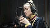 En student står å synger konsentrert inn i en mikrofon. Hun har store hodetelefoner på seg.