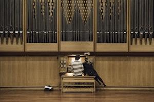 En student sitter å spiller på et stort orgel. En lærer lener seg moot ham og peker på notearket.