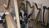 En studenter sitter smilende og spiller på en stor harpe. Læreren sitter rett ved siden av og smiler.