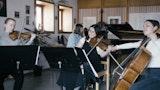 Fire studenter spiller sammen i et ensemble: En på fiolin, en på bratsj, en på cello og en spiller klaver.