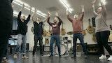 Fem studenter og en lærer står smilende i ring med armene opp i et musikkrom.