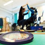 Musikkterapeut trener med en funksjonshemmet person