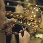 Nærbilde av en skinnende blank trombone som blir spilt på