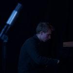 Øystein Folkedal sitter spiller piano i mørket.