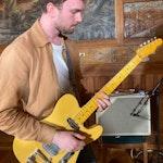 Øyvind spiller el-gitar. Bak han er en forsterker mikket opp.