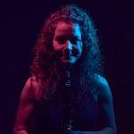 Mørkt bilde med lilla lys, av Daniela Braun med klarinett.