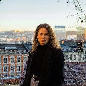 Elise står på en tak og ser inn i kameraet. Bak henne ser man Oslo.