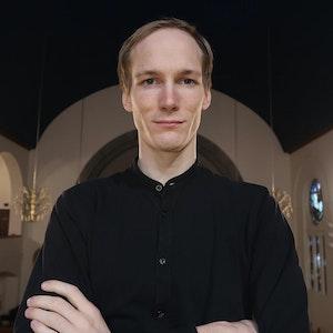 Espen Takle står med armene i kors i en kirke og stirrer direkte inn i kameraet.