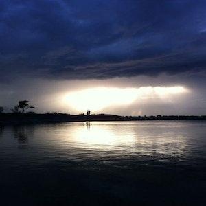 Solen bryter gjennom tunge skyer over et mørklagt vann