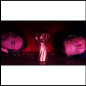Frank Havrøy og Erik Dæglin med hodene mot hverandre og knyttneveskulptur mellom seg, i rosa lys