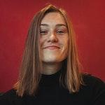 Fride Nøstdahl Hjelle smiler foran rød vegg.