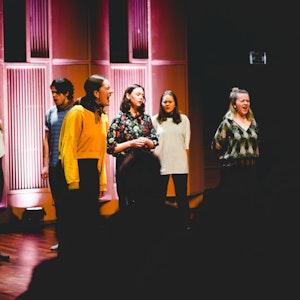 Medlemmene i Full hals står på en scene og synger