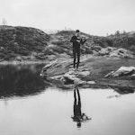 Henrik Nordtun Gjertsen spiller fele ved en innsjø