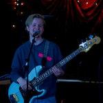 Joachim står på en scene og spiller på en el-bass og synger i en mikrofon.