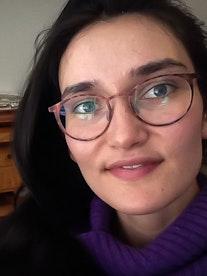 Portrettbilde av Johanna Scheie Orellana. Hun har på seg briller og ser smilende inn i kameraet.