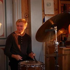 Jon Espelid smiler mens han spiller trommesett.