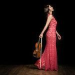 Kelly Sohyoung Lee i rød kjole med fiolin, på mørk parkett.