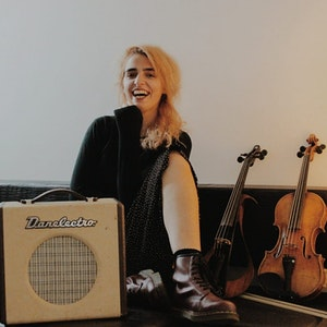 Larissa Terescenko sitter langs veggen ved siden av fioliner og en forsterker
