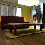 Minimalistisk foto av stue, med sofa, teppe og sofabord, med gulaktige fargenyanser