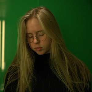 Alvorlig bilde av Marie Lemme som ser ned, foran grønn vegg.