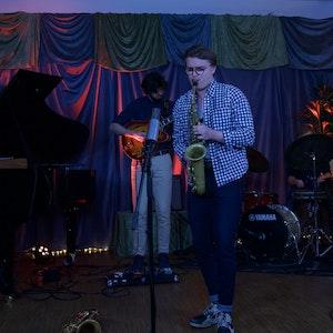Oskar står på en scene og spiller saksofon inn i en mikrofon.