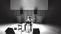Robert sitter og spiller gitar på en scene. Foran seg har han et notestativ og to monitorer.