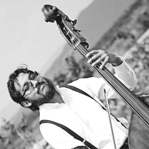 Rodrigo Mata står i landskap med kontrabassen