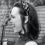 Nærbilde i profil av en glisende Sabine Kronberger med fiolin.