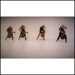 Fire cellister står foran lys bakgrunn og spiller på celloene